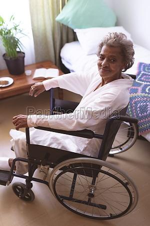 happy senior woman sitting in wheelchair