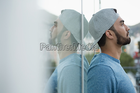 handsome man leaning on glass
