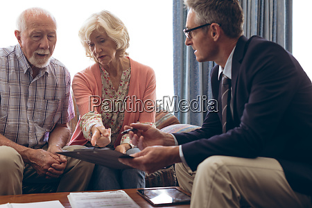 male physician interacting with senior couple