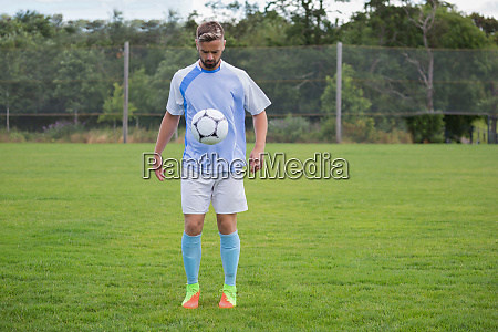 football player juggling soccer ball