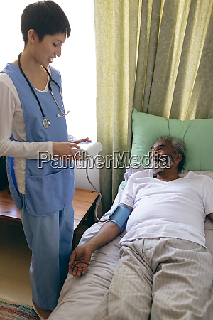 female nurse checking blood pressure of
