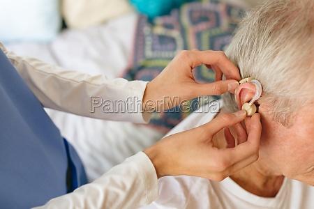 female nurse applying hearing aid to