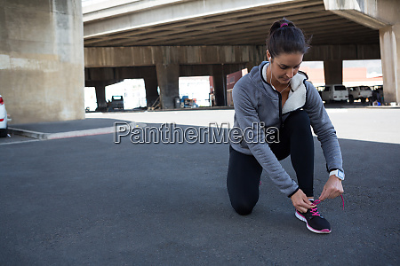 female jogger tying her shoe laces