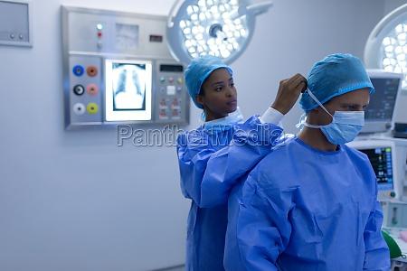 female surgeon helping male surgeon to