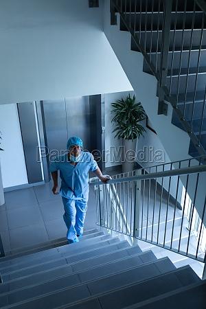 male surgeon walking upstairs in hospital