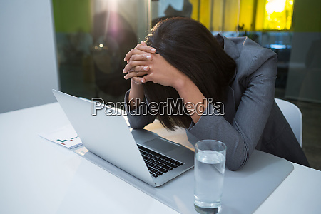tensed businesswoman sitting with laptop at