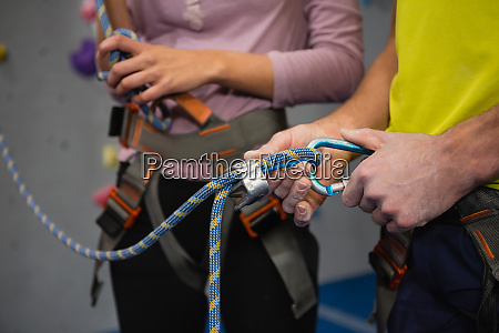midsection of athletes adjusting safety harness