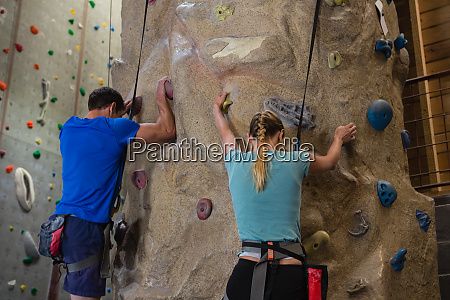 rear view of athletes rock climbing