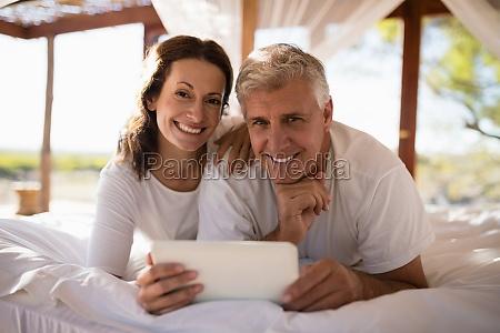 portrait of happy couple using digital