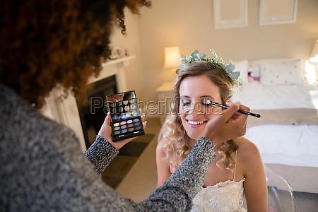 woman applying makeup to bride in