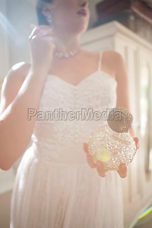 beautiful bride holding perfume while wearing