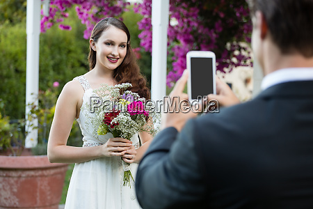 bridegroom photographing bride holding bouquet at
