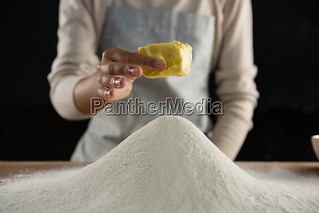 woman adding butter cube into flour