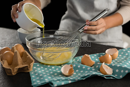 woman adding oil into beaten eggs