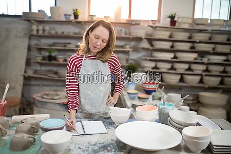 female potter checking the orders in