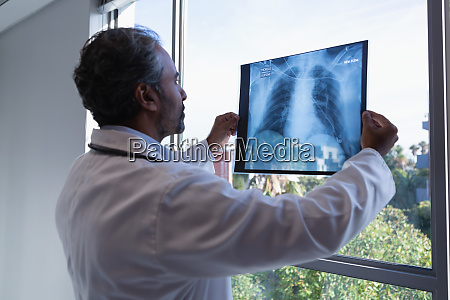 male doctor looking at x ray