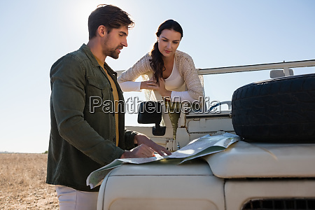 couple reading map on off road