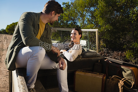 smiling couple sitting in off road