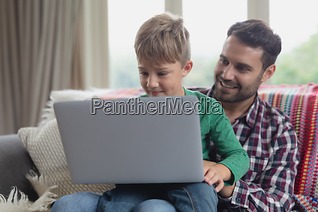 father and son using laptop on
