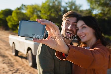 happy woman taking selfie with man