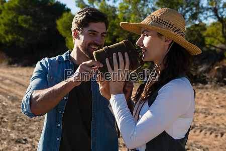 young man assisting girlfriend drinking water