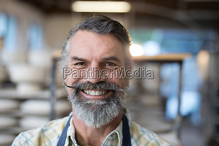 happy male potter standing in pottery