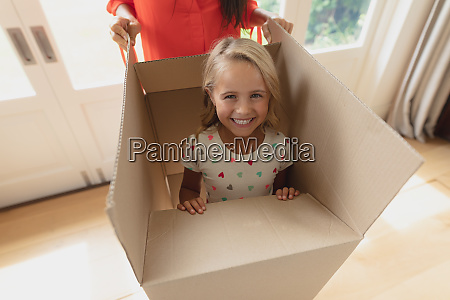 mother and daughter playing with cardboard