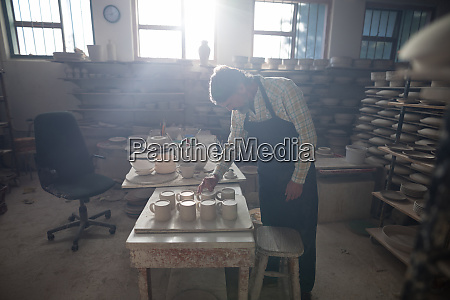 male potter checking craft product