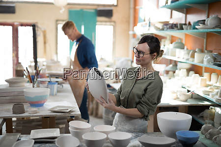 female potter checking craft product