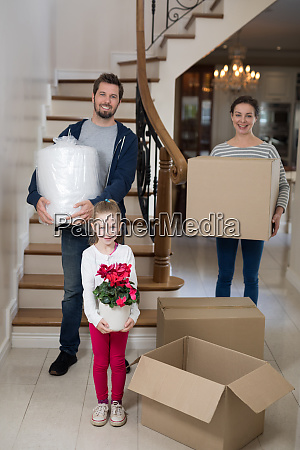 parents and daughter opening cardboard boxes