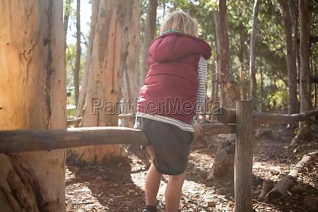 little girl sitting on log of