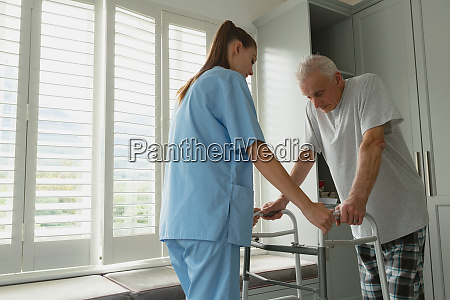 female doctor helping active senior man