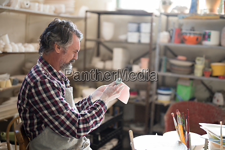 male potter painting bowl