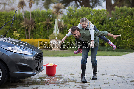 teenage girl and father washing a