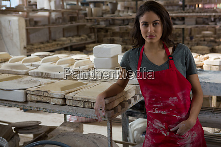 confident female potter standing in pottery