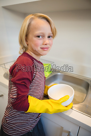 boy washing utensil in kitchen