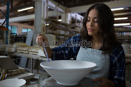 female potter decorating bowl with paint