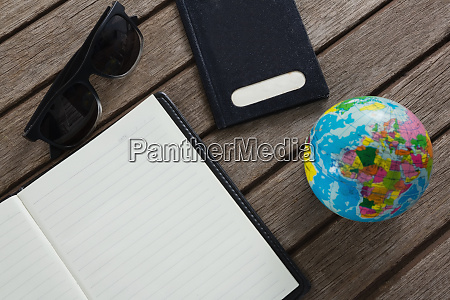 open diary surrounded with travelling accessories