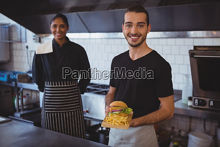 portrait of waiter with coworker holding