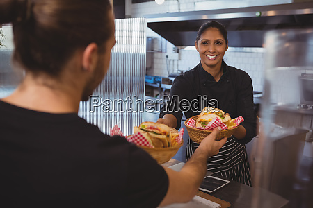 smiling waitress giving baskets with food