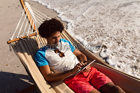 man using digital tablet while relaxing
