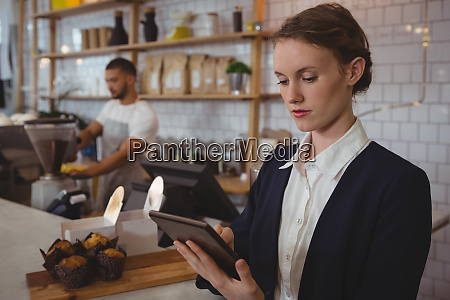 owner using tablet with waiter working