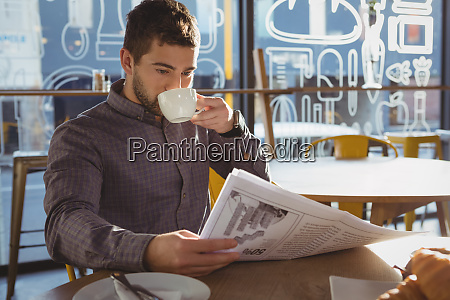 businessman reading newspaper while drinking coffee
