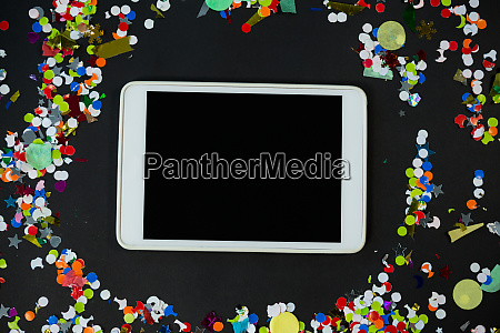digital tablet surrounded by confetti