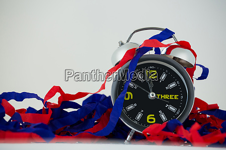 alarm clock and streamers against white