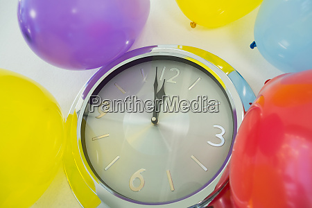 balloons and clock hands reaching 12