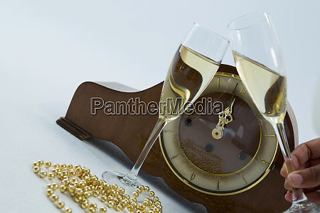 champagne glass and clock on white