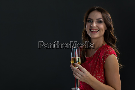 smiling woman holding glass of champagne