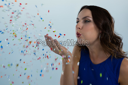 woman blowing colorful glitter in the
