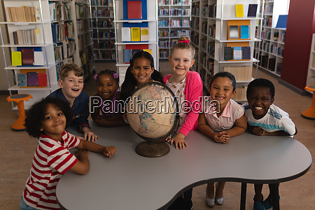 happy schoolkids with globe looking at